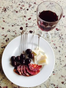 olives, cheese, salami on a white plate with a glass of red wine  Image courtesy of Amore Cucina